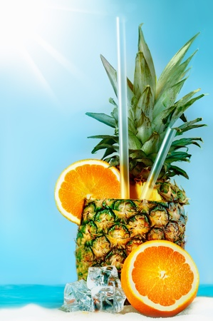 Pineapple with oranges and tubules on white beach sand  Fresh cold drink Stock Photo - 13089691