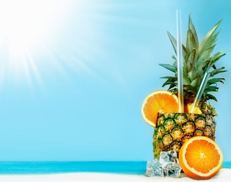 nue plage: Ananas frais avec les oranges, les tubules et de la glace sur la plage ensoleill�e avec copie espace