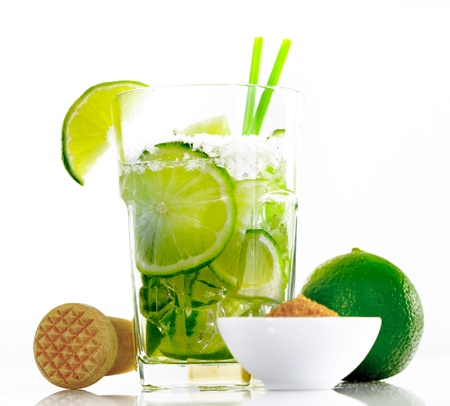 caipirinha: Caipirinha isolated on white background, with a mortar and brown sugar and sliced limes Stock Photo