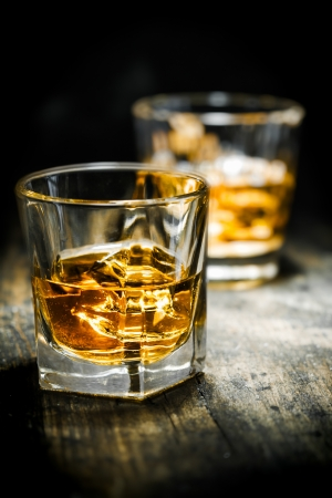 whiskey glass: Whisky or Whiskey, vintage style, on a wooden plate