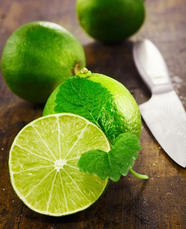 Caipirinha and Mojito accessories. Fresh limes with mint sliced with a knife on a wooden background photo