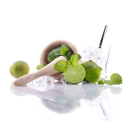 drinkable: Caipirinha Ingredients with mortar and pestle and fresh lime. Aside an empty glass with ice cubes. For Drinkable Concepts