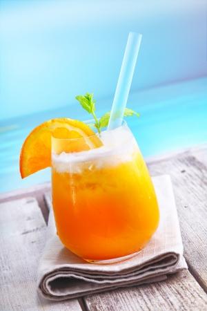 coctel de frutas: Refrescante helado de pie coctel de naranja en una terraza de madera con vista al mar de vacaciones en un resort tropical Foto de archivo