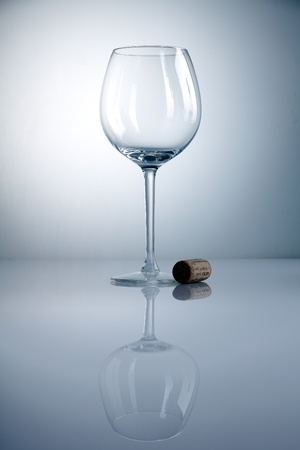 Empty wine glass with cork and reflexion on a blue background photo