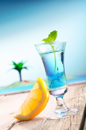 pool deck: Blue Curacao Beach Cocktail with fresh lemon standing on a landing stage, with the pacific and a lagoon with a palm in the background. More Drinks in my portofolio. Stock Photo
