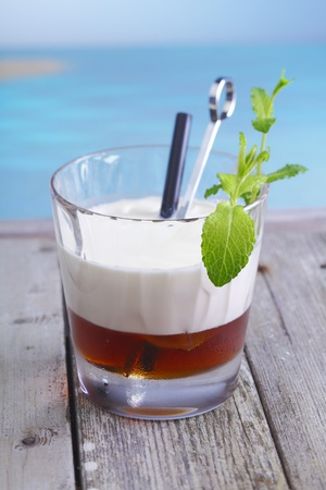 White Russian Coffee Cocktail with ice cubes and cream topping standing in a lounge at the beach, for alcoholic Drink Concepts. Visit my portfolio for more inspirations. photo
