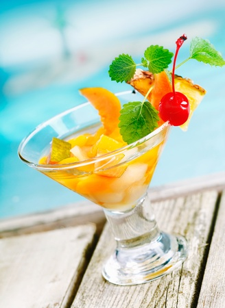 Refreshing colourful tropical fruit cocktail appetiser in a conical glass filled with pieces of fresh mixed fruit on decking alongside a blue pool Stock Photo - 13221622