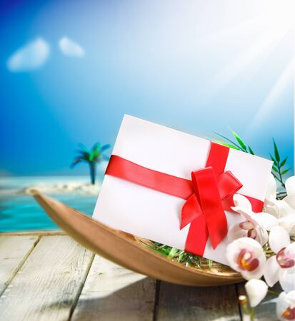Romantic gift or envelope decorated with red ribbon and a bow on a wooden deck overlooking the ocean in a in tropical paradise photo