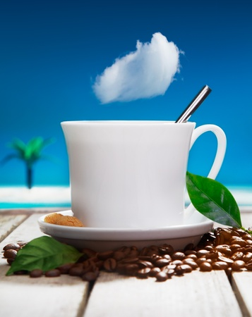 brewed: Freshly brewed cup of aromatic coffee with fresh coffee beans on a wooden deck overlooking the ocean at a tropical resort
