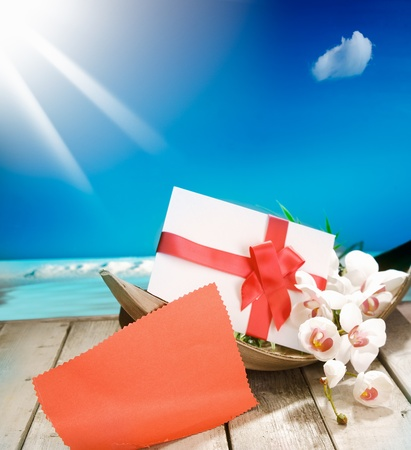 Voucher in a palm bowl with a bow at a deck in front of the deep blue pacific ocean and a shiny sun. With copyspace for your own Text and messages photo