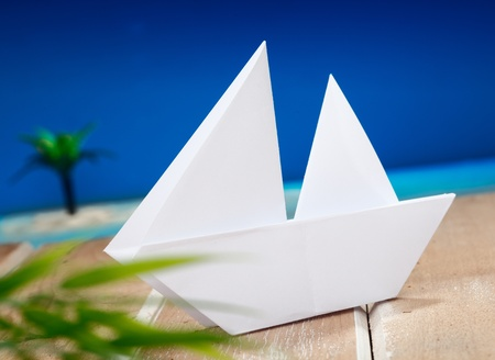 boat party: a paper boat on a wooden table in front of a beach with a palm on an idyllic place. Maybe for holiday vacation or wellness concepts