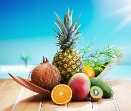 Frische Früchte am Strand auf einem Deck vor einer Insel mit einer Palme. Verschiedene tropische Früchte, Orange, Ananas oder Ananas, Limette, Mango und Avocado.