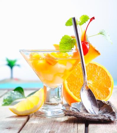 coctel de frutas: C�ctel de frutas ex�ticas colorida de frutas tropicales frescas se presentan con una cuchara de servir en un descanso en un resort de lujo