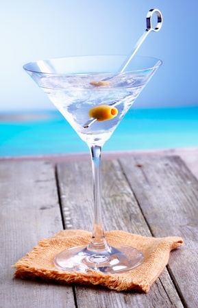 south pacific: Refreshing martini cocktail in a conical glass with olive garnish served on a summer deck overlooking the ocean Stock Photo