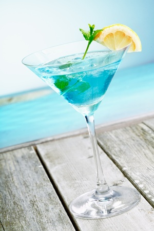 curacao: Refreshing classical blue curacao martini cocktail garnished with fresh lemon and served alongside the ocean on a tropical vacation