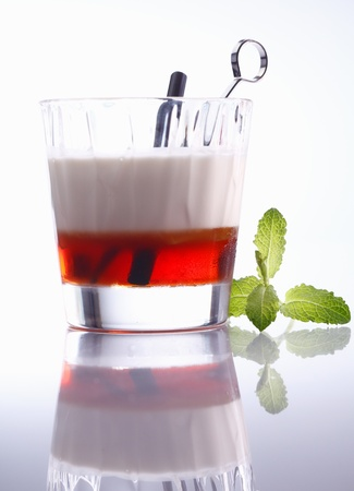Low angle view of a layered alcoholic cocktail in a tumbler with reflection, background graduating white to grey photo