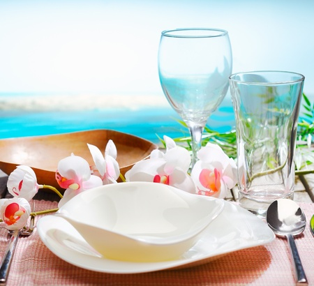 Stylish place setting with orchids and beautiful modern dinnerware in an exotic beachfront restaurant