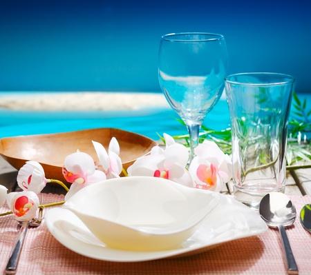 Decoratieve tropische tafel instelling met stijlvol servies en orchideeën met uitzicht op de oceaan op een resort restaurant Stockfoto