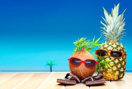 Twee fruitige vrienden, een kokosnoot en ananas, met leuke bladeren haistyles en trendy zonnebril in tropisch paradijs Stockfoto