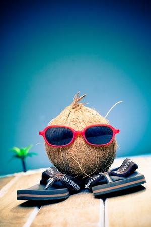 frutas divertidas: La imagen humorística de un caballero de coco turística por sus gafas de sol de moda rojas en sus vacaciones de verano en el trópico Foto de archivo