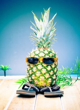 Comical character of a cool dude pineapple in his trendy sunglasses and slip slops out enjoying the tropical sunshine photo