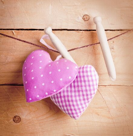 Two pretty pink fabric country hearts hanging on wooden pegs in a romantic Valentines, wedding or anniversary concept