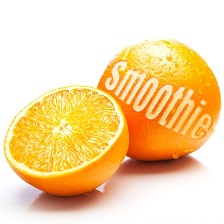 Fresh oranges with one halved to show the juicy pulp and the other whole with the word Smoothie cut out of the rind in an orange smoothie concept photo