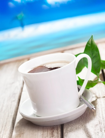atilde: Refreshing cup of coffee served against a blue tropical coastline on a summer vacation