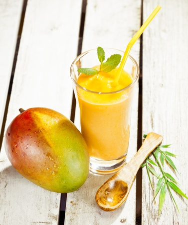 fruit shake: High angle view of a glass of healthy fresh mango smoothie with a delicious ripe whole fruit alongside on wooden decking