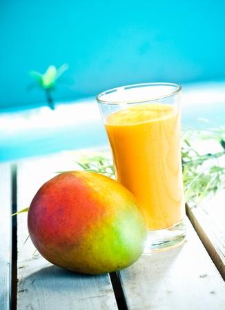 Creamy Mango-Smoothie mit frischen Mango-Saft gemischt und Joghurt serviert mit Blick auf einen tropischen Ozean