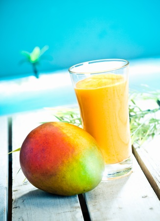 Creamy mango smoothie with blended fresh mango juice and yoghurt served overlooking a tropical ocean Stock Photo