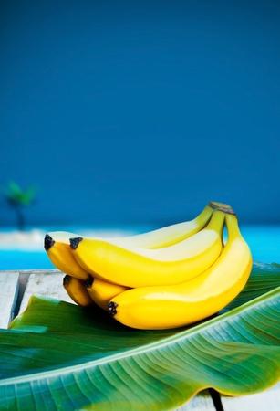 海を背景にバナナの葉で熟したトロピカル バナナの束 写真素材