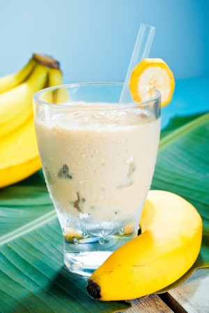 fruit smoothie: Creamy banana smoothie blended with fresh yoghurt in a glass with ripe bananas and a banana leaf