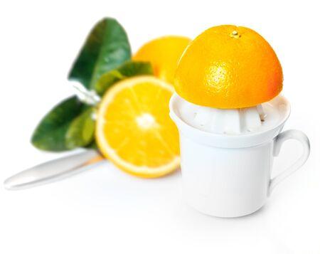 Squeezing fresh healthy orange juice on a plastic juicer using halved oranges Stock Photo