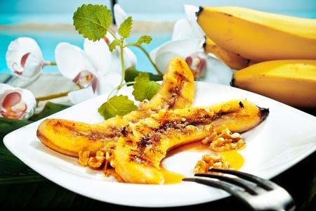 おいしい黄金の茶色の焼きバナナと白い大皿にクルミ デザート 写真素材