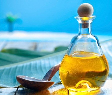 Bottle of glowing golden oil and a ladle on a deck near the sea ready for a tropical spa treatment Stock Photo - 13385369