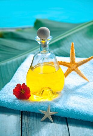 Bottle of golden essential oil plant extract on a towel alongside a pool ready for an aromatherapy spa treatment Stock Photo - 13385383