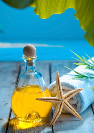 body oil: A decanter of golden aromatherapy oil , starfish and towel stand on a wooden deck above the sea in a marine spa treatment and wellness concept