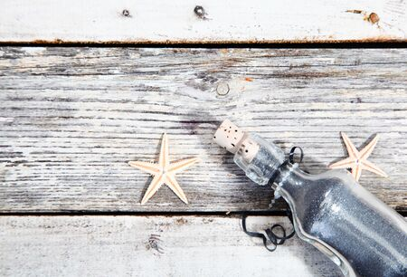 corked: Nautical background with starfish and a clear glass corked bottle on weathered timber planks with woodgrain