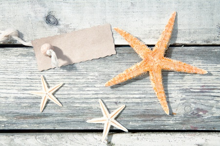 Nautical starfish background with three sea stars on weathered timber planks with a blank label for your text photo