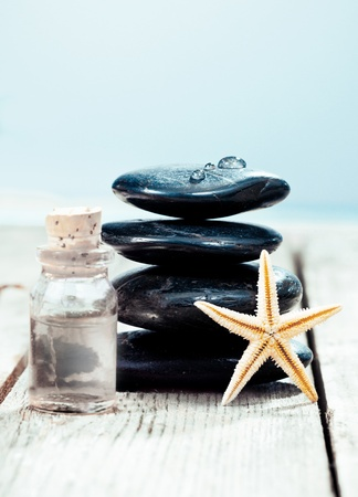 Balanced column of smooth black spa massage stones with a bottle of essential oil ready for a luxurious hot rock massage photo