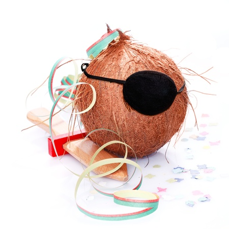 Coconut with an eye patch, confetti and a paper streamer. For little Pirates and caribbean and tropical concepts. Stock Photo - 13498399