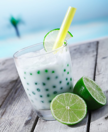 Fresh tapioka pearls tea with lime sirup standing in front of the beach on a wooden plate photo
