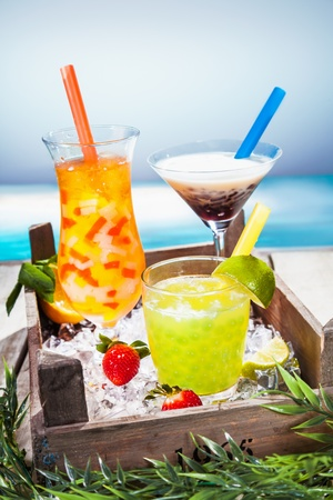 Trio of colourful tropical cocktails blended with fruit in different shaped glasses served overlooking a tropical beach photo