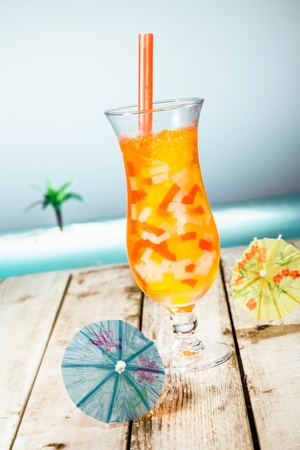 Mango Boba Cocktail Tea standing in front of a beach background with beautiful paper umbrellas. photo