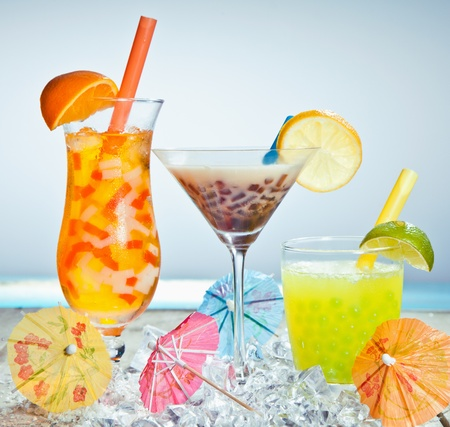 Three different boba tea cocktails with mango, orange, coffee and lime flavored. With paper umbrellas. photo
