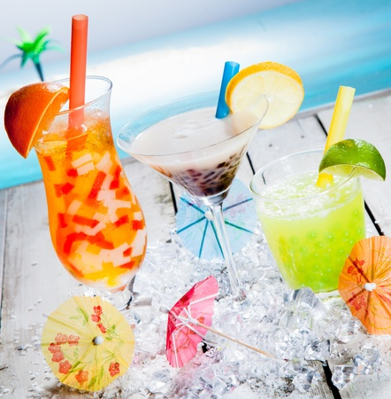 Three different colourful tropical fruit bubble tea sorts served chilled on a bed of crushed ice as a welcome refreshment at a beachfront resort photo