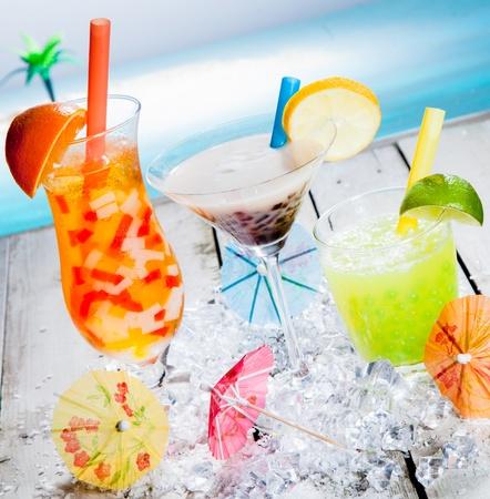bebidas alcohÓlicas: Tres diferentes colores de frutas tropicales tipo té de la burbuja sirve frío sobre una cama de hielo picado como un refresco de bienvenida en un resort frente al mar Foto de archivo