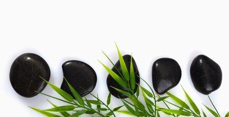 A row of spa massage stones and bamboo leaves on a white background with copyspace photo