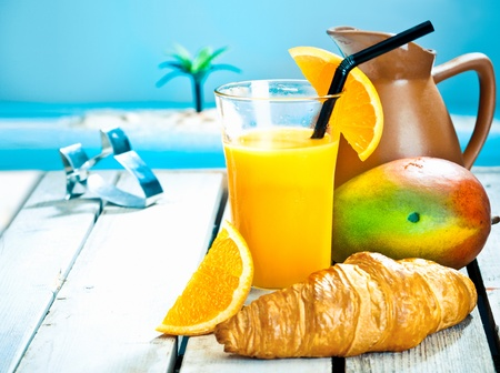 Tropical breakfast still life with a healthy mango and orange smoothie and a fresh ripe mango with a golden croissant against a blue ocean backdrop Stock Photo
